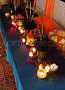 Moroccan table setting with cozy cushioned seats, warmly lit by colourful tea lights.