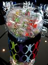 Simple table centrepieces using fishbowls filled with lollies on branded elevations.